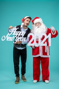 Vue de face du père noël avec homme tenant bonne année et planches 2021 sur mur bleu