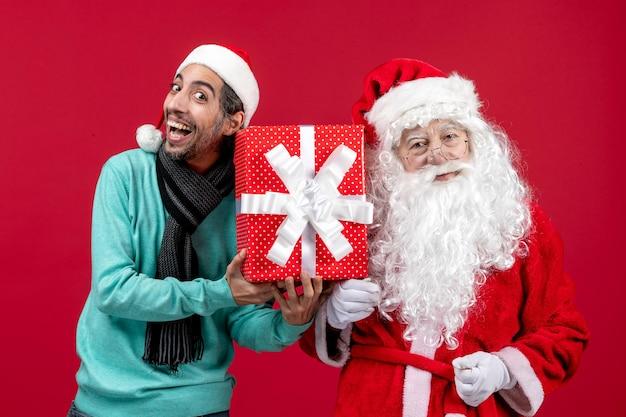 Vue de face du père noël avec un homme tenant un cadeau de vacances sur l'émotion rouge cadeau rouge noël nouvel an