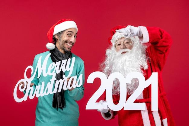 Vue de face du père noël avec un homme tenant et joyeux noël écrits sur l'émotion du nouvel an rouge