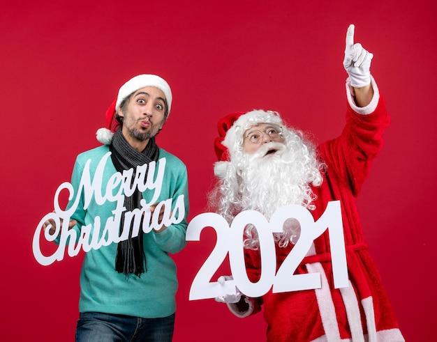 Vue de face du père noël avec un homme tenant et joyeux noël écrits sur les émotions du nouvel an rouge