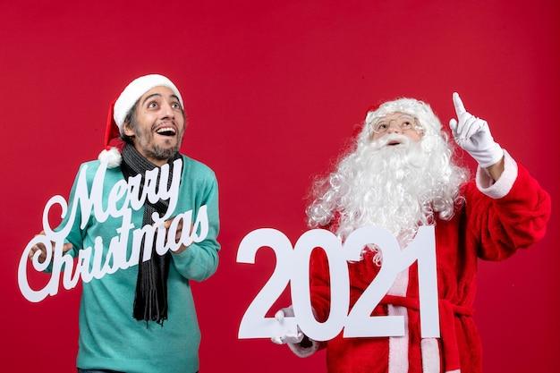 Vue de face du père noël avec un homme tenant et joyeux noël écrits sur rouge présente le nouvel an
