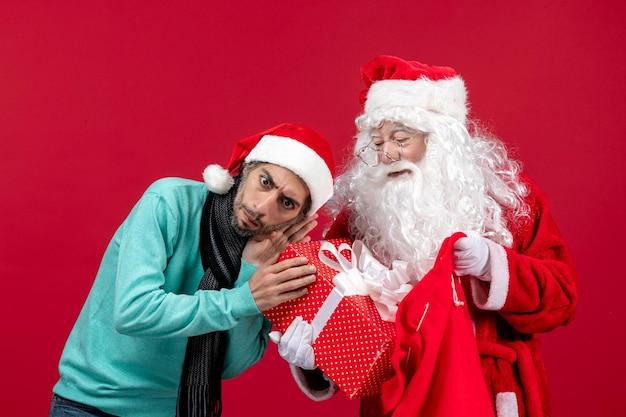 Vue de face du père noël avec un homme tenant le présent du sac sur une couleur de vacances de nouvel an émotion de noël rouge