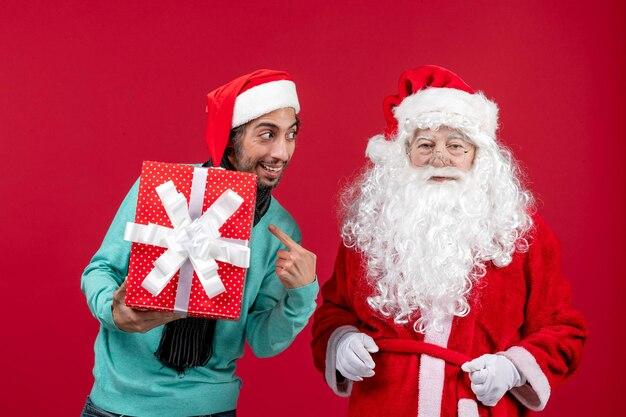 Vue de face du père noël avec un homme tenant des vacances présentes sur les cadeaux rouges émotion rouge noël nouvel an