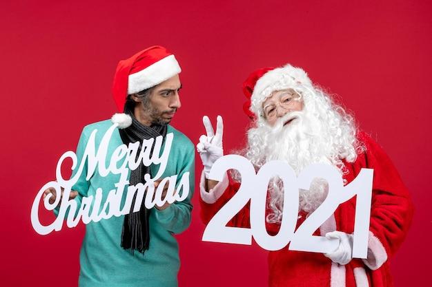 Vue de face du père noël avec des hommes tenant et joyeux noël écrits sur noël rouge du nouvel an
