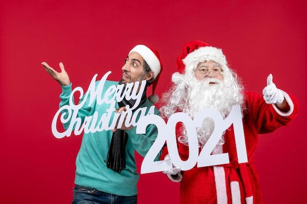 Vue de face du père noël avec des hommes tenant et joyeux noël écrits sur noël rouge nouvel an