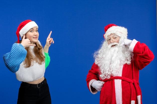 Vue de face du père noël avec une jeune femme debout sur le bleu présente l'émotion du nouvel an