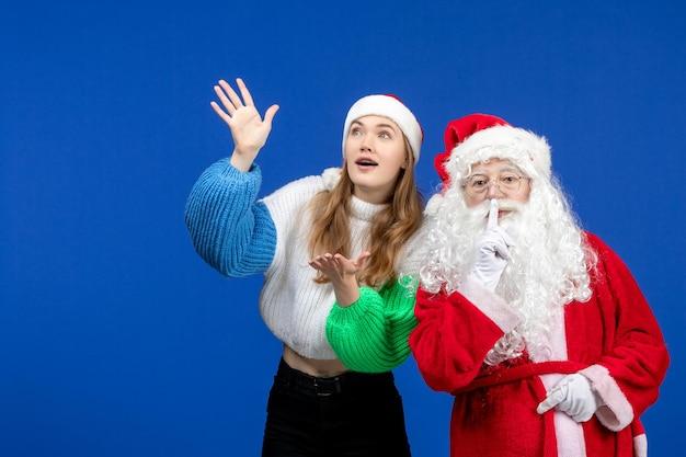 Vue de face du père noël avec une jeune femme debout sur le bleu des vacances du nouvel an couleur noël émotion