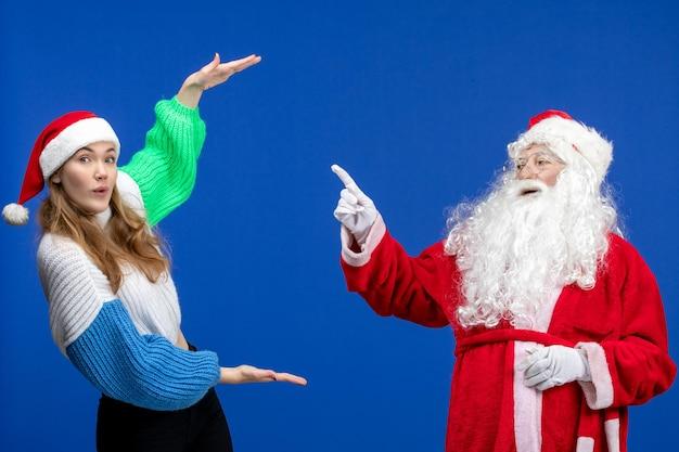 Vue de face du père noël avec une jeune femme debout sur le modèle de vacances du nouvel an bleu
