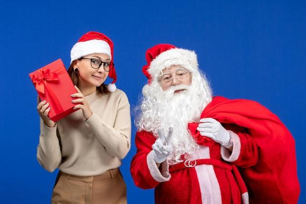 Vue de face du père noël avec une jeune femme portant un sac de cadeaux sur un bureau bleu émotion couleur neige de noël