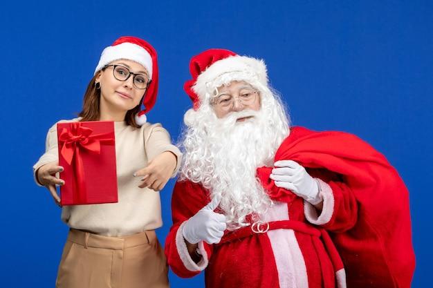 Vue de face du père noël avec une jeune femme portant un sac de cadeaux sur la couleur bleue de l'émotion des vacances