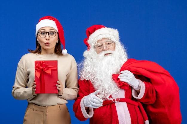 Vue de face du père noël avec une jeune femme portant un sac de cadeaux sur la couleur bleue de l'émotion