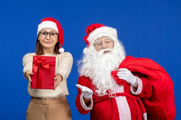 Vue de face du père noël avec une jeune femme portant un sac de cadeaux sur la couleur bleue des émotions