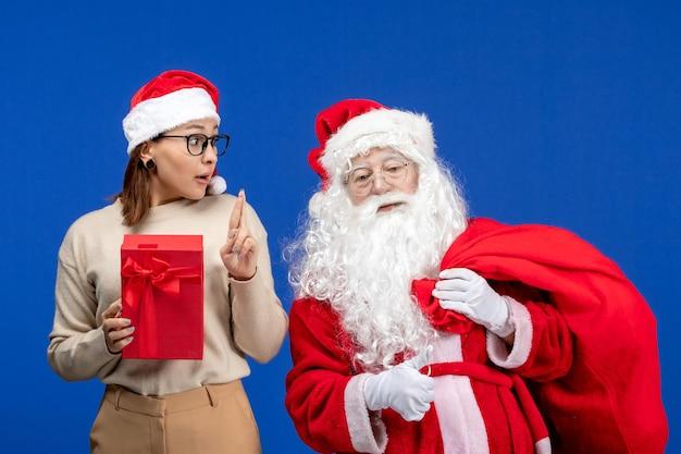 Vue de face du père noël avec une jeune femme portant un sac de cadeaux sur la neige de noël couleur émotion bleue
