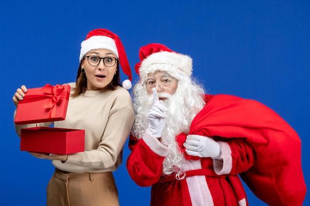 Vue de face du père noël avec une jeune femme qui s'ouvre présente sur l'émotion de neige des vacances de bureau bleu
