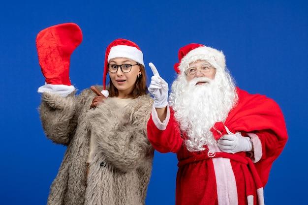 Vue de face du père noël avec une jeune femme sac de transport plein de cadeaux sur bleu