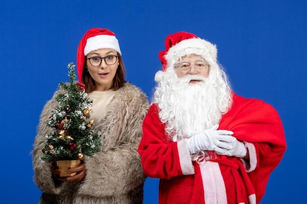 Vue de face du père noël avec une jeune femme sac de transport plein de cadeaux le nouvel an de couleur bleue