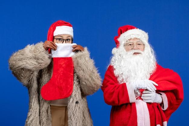 Vue de face du père noël avec une jeune femme sac de transport plein de cadeaux pendant les vacances du nouvel an bleu