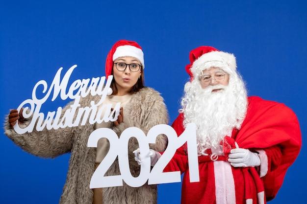 Vue de face du père noël avec une jeune femme tenant un joyeux noël et des écrits sur les vacances bleues