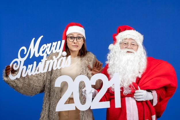 Vue de face du père noël avec une jeune femme tenant un joyeux noël et des écrits sur les vacances du bureau bleu