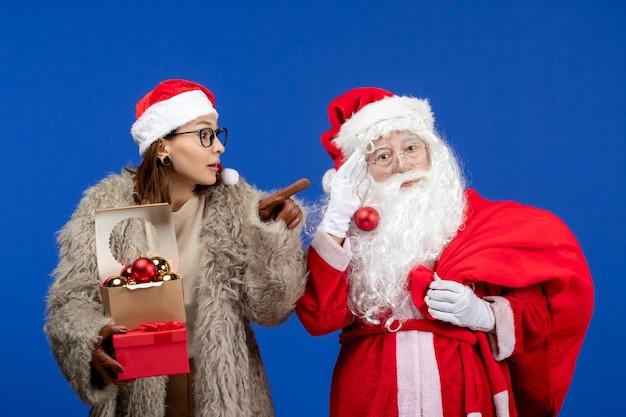Vue de face du père noël avec une jeune femme tenant un sac avec des cadeaux et des jouets sur un bureau bleu