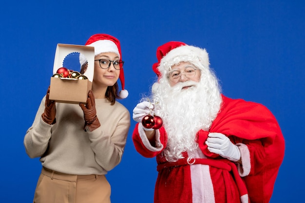 Vue de face du père noël avec une jeune femme tenant un sac avec des cadeaux et des jouets sur une couleur bleue du nouvel an de noël