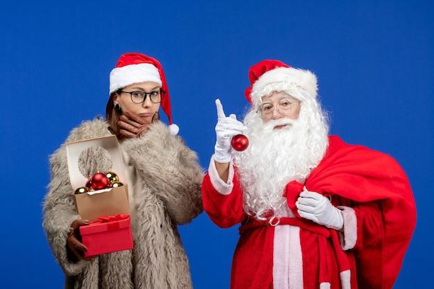 Vue de face du père noël avec une jeune femme tenant un sac avec des cadeaux et des jouets pendant les vacances bleues couleur de noël nouvel an