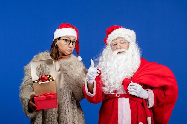 Vue de face du père noël avec une jeune femme tenant un sac avec des cadeaux et des jouets sur les vacances bleues couleur de noël nouvel an