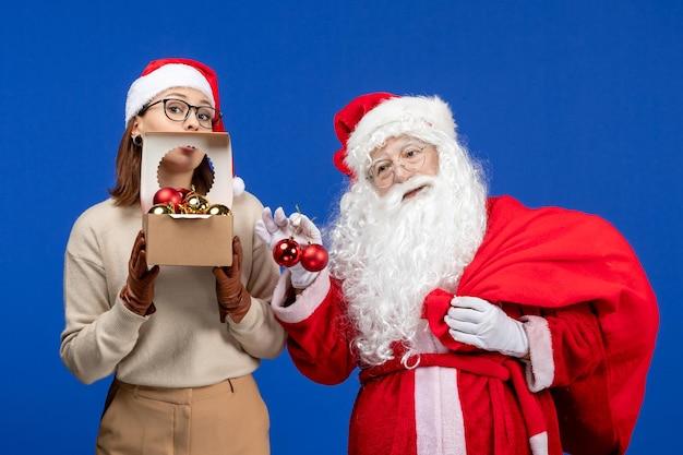 Vue de face du père noël avec une jeune femme tenant un sac avec des cadeaux et des jouets sur les vacances bleues de noël