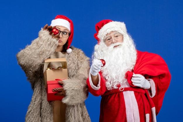 Vue de face du père noël avec une jeune femme tenant un sac avec des cadeaux et des jouets en vacances de bureau bleu