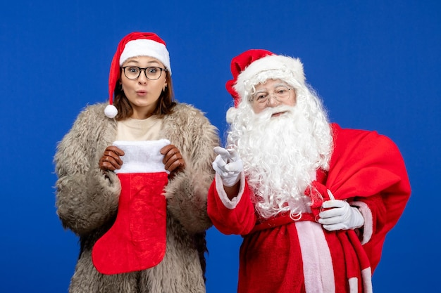 Vue de face du père noël avec une jeune femme tenant un sac présent et une chaussette rouge sur la couleur bleue de noël
