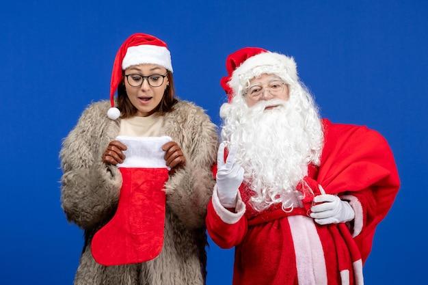 Vue de face du père noël avec une jeune femme tenant un sac présent et une chaussette rouge sur une émotion de couleur bleue