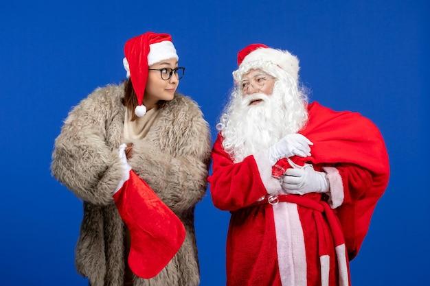 Vue De Face Du Père Noël Avec Une Jeune Femme Tenant Un Sac Présent Et Une Chaussette Rouge Sur Les Vacances Bleues De Noël Photo gratuit