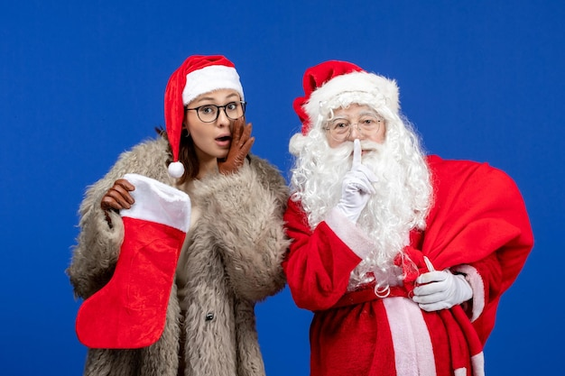 Vue de face du père noël avec une jeune femme tenant un sac présent et une chaussette rouge sur les vacances bleues de noël