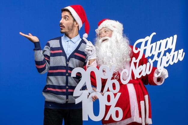 Vue de face du père noël avec un jeune homme tenant une bonne année et des écrits en pourcentage sur le mur bleu