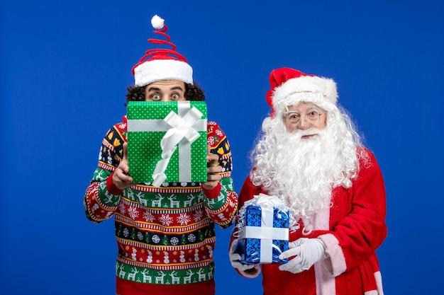 Vue de face du père noël avec un jeune homme tenant des cadeaux de noël sur le mur bleu