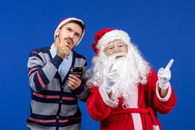 Vue de face du père noël avec un jeune homme tenant une carte bancaire sur le mur bleu