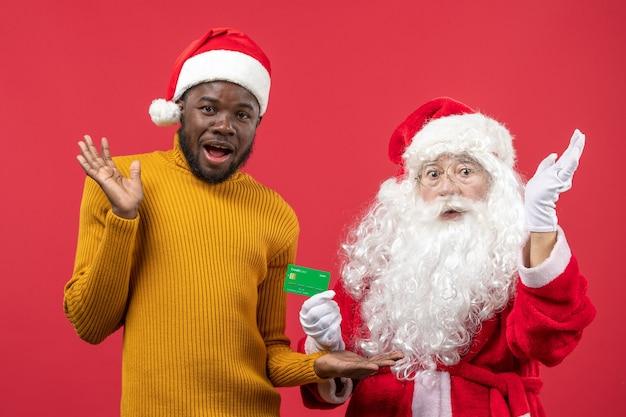 Vue De Face Du Père Noël Avec Jeune Homme Tenant Une Carte Bancaire Verte Sur Le Mur Rouge Photo gratuit