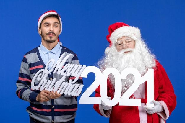 Vue de face du père noël avec un jeune homme tenant et joyeux noël écrits sur le cadeau de vacances de noël bleu nouvel an