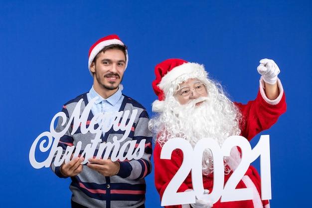 Vue de face du père noël avec un jeune homme tenant et joyeux noël écrits sur la couleur bleue noël nouvel an