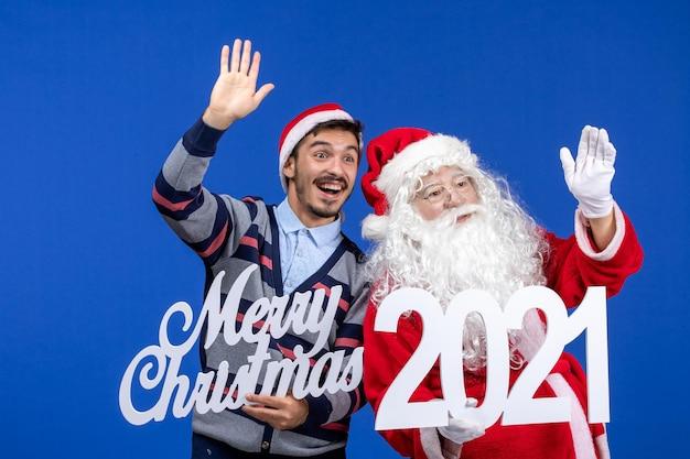 Vue de face du père noël avec un jeune homme tenant et joyeux noël écrits sur le nouvel an de couleur bleue