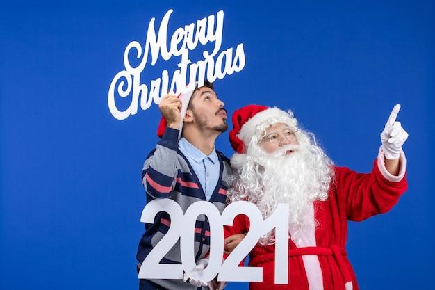 Vue de face du père noël avec un jeune homme tenant et joyeux noël écrits sur les vacances présentes bleues