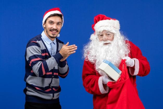 Vue de face du père noël avec un jeune homme tenant un sac de cadeaux sur un mur bleu