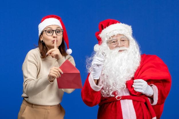 Vue de face du père noël et de la lettre d'ouverture de la jeune femme sur les vacances bleues de l'émotion du nouvel an de noël
