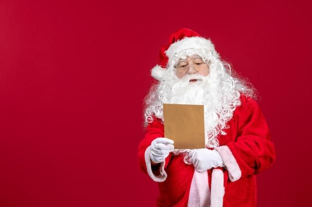 Vue de face du père noël lisant la lettre d'un enfant sur l'émotion de vacances de noël présente rouge