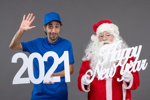 Vue de face du père noël avec messager masculin tenant bonne année et planches 2021 sur le mur gris