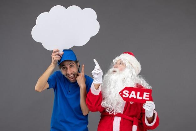 Vue de face du père noël avec messager masculin tenant signe de nuage blanc et vente sur mur gris