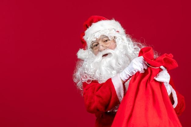Vue de face du père noël ouvrant un sac plein de cadeaux pour les enfants en vacances rouges émotion de noël