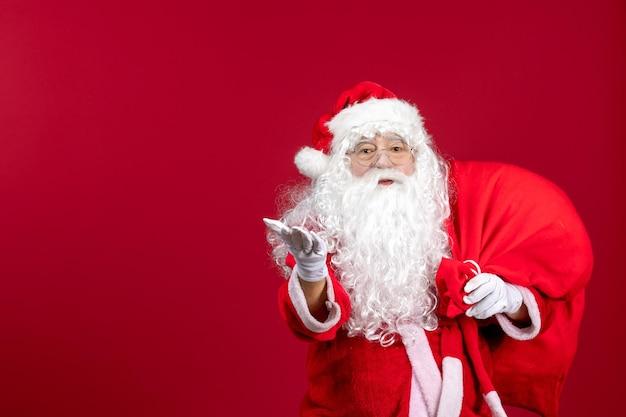Vue de face du père noël portant un sac rouge plein de cadeaux sur les émotions rouges vacances de noël du nouvel an