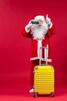 Vue de face du père noël avec sac jaune prendre des photos avec appareil photo sur le mur rouge