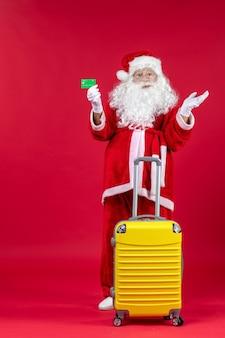 Vue De Face Du Père Noël Avec Sac Jaune Tenant Une Carte Bancaire Verte Sur Le Mur Rouge Photo gratuit